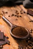 Dark roasted pure arabica coffee beans and ground coffe on the w Royalty Free Stock Images