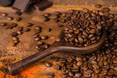 Dark roasted pure arabica coffee beans and ground coffe on the w. Dark roasted pure arabica coffee beans and ground coffe in old spoon on the wooden table, copy Stock Photo