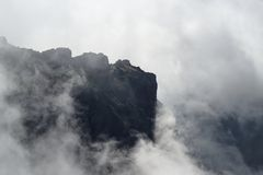 Dark rock formation inside of raised clouds. View from Pico do Arieiro on Portuguese island of Madeira royalty free stock photo