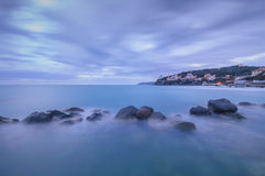 Dark Rocks in a blue ocean on twilight. Castiglioncello, Italy Stock Image