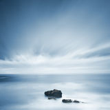 Dark rocks in a blue ocean under cloudy sky in a bad weather. Long exposure photography Stock Photo