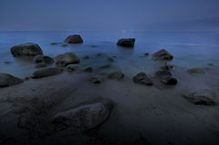 Dark rocks in a blue ocean under cloudy sky in a bad weather. Long exposure photography Royalty Free Stock Image