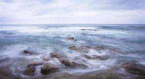 Dark rocks in a blue ocean under cloudy sky. Seascape image of rough seas and waves with rocks Royalty Free Stock Photo