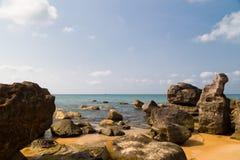 Dark rocks and blue sea Stock Image