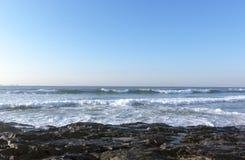 Dark Rocks  Ocean Waves and Blue Skyline Seascape Stock Images