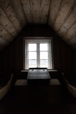 Dark room. Dark wooden attic room with desk by window Royalty Free Stock Photos