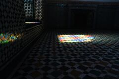 Dark room decorated with tiles and mosaic while light enters from a window
