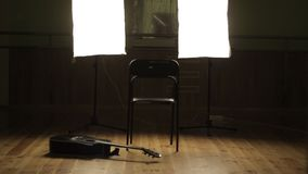 Dark room with a guitar. The musician enters a dark room. On the floor is a black acoustic guitar stock video footage