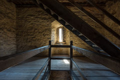 Dark room with stone walls window and wooden staircase Royalty Free Stock Images