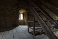 Dark room with stone walls window and wooden staircase Stock Images