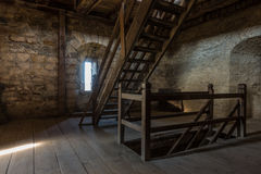 Dark room with stone walls window and wooden staircase Royalty Free Stock Photos