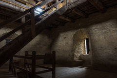 Dark room with stone walls window and wooden staircase Royalty Free Stock Image