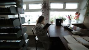 Woman in a dark room. In a dark room at the table, a woman is sitting and reading a book stock video footage