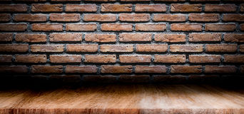 Dark room with wooden floor and brick wall background. Royalty Free Stock Photo