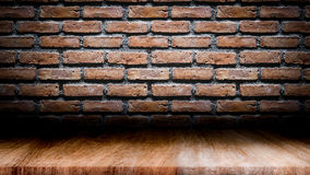 Dark room with wooden floor and brick wall background. Royalty Free Stock Photography