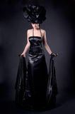 Dark rose. Full-length dark portrait of a girl in a black dress and a rose hat Stock Photo