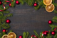 Dark rustic wood table flatlay - Christmas background with decoration and fir branch frame. Top view with free space for copy. Text stock photography