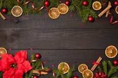 Dark rustic wood table flatlay - Christmas background with decoration and fir branch frame. Top view with free space for copy. Text stock image
