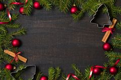 Dark rustic wood table flatlay - Christmas background with decoration and fir branch frame. Top view with free space for copy. Text royalty free stock photo
