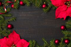 Dark rustic wood table flatlay - Christmas background with decoration and fir branch frame. Top view with free space for copy. Text stock images