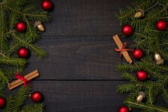 Dark rustic wood table flatlay - Christmas background with decoration and fir branch frame. Top view with free space for copy stock images