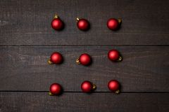 Dark rustic wood table flatlay - Christmas background with red christmas ornaments. Top view with free space for copy text stock images