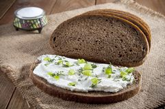 Dark rye bread, sandwich with cream, chives and dill and salt in saltshaker on burlap. Close-up.  stock image