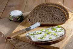 Dark rye bread, sandwich with cream and knife on wooden cutting board and salt in saltshaker on burlap. Close-up.  royalty free stock photography