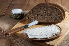 Dark rye bread, sandwich and knife on wooden cutting board and salt in saltshaker on burlap.  royalty free stock photos