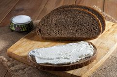 Dark rye bread and sandwich on wooden cutting board and salt in saltshaker on burlap.  royalty free stock images