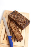 Dark rye bread whith knife on a board. On white Stock Photos