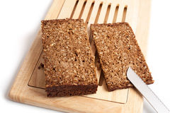 Dark rye bread whith knife on a board. On white Royalty Free Stock Photos
