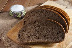 Dark rye bread on wooden cutting board and salt in saltshaker on burlap. Dark rye bread on wooden cutting board and salt in saltshaker on sackcloth stock image
