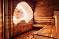 Dark sauna with ergonomic cocoon with a salt wall. Red, dark sauna with ergonomic cocoon with a salt wall royalty free stock images