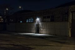 Dark scary alley at night with gated door warehouse entrance. Stock Images