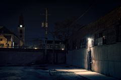 Dark scary alley at night with warehouse entrance Royalty Free Stock Photo