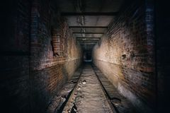 Dark scary corridor in abandoned industrial ruined brick factory, creepy interior. Perspective toned Royalty Free Stock Photography