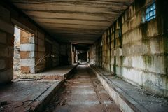 Dark scary corridor in abandoned industrial ruined brick factory, creepy interior. Perspective toned Royalty Free Stock Image