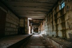Dark scary corridor in abandoned industrial ruined brick factory, creepy interior, perspective. Toned Royalty Free Stock Image