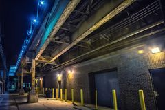 Dark and scary downtown urban city street alley at night royalty free stock photo