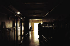 Dark and scary hallway. A darkend black hallway in a school at night a girl standing at the end looking stock photography