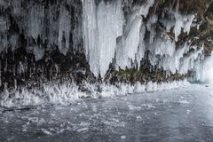 Dark and scary icicles in the a cave and broken ice pieces. Several sharp icicles hanging from the cave ceiling. The weather is cold and freezing with some Royalty Free Stock Photography