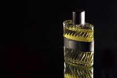 Dark scent. Yellow perfume on black background Stock Image