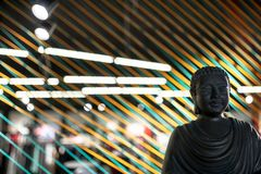 Bust of Buddha in illuminated interior with colorful ropes lines installation stock photography