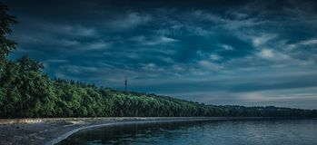 Dark Seafront. Embankment quay seafront levee landscape river clouds overcast the trees wood royalty free stock image