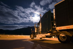 Dark semi truck reefer in night light with moony clouds. Colorful picture of a black semi truck and a reefer trailer standing in the parking lot at night, lit a Royalty Free Stock Image