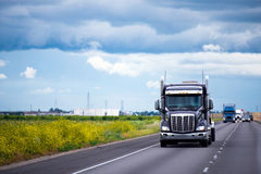 Dark semi truck with traffic on road in California Royalty Free Stock Photos