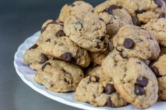 Dark and Semisweet Chocolate Chip Cookies. Homemade chocolate chip cookies with dark and semisweet chocolate chips on a white dish and dark background royalty free stock photo