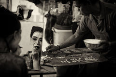Dark sepia version of Chinese Teochew opera singer makeup and man writing the programme for the day Royalty Free Stock Photos