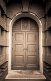 Dark sepia view of Closed green wooden door in European style with Brown building Royalty Free Stock Photos